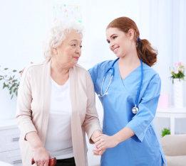 nurse and senior woman in light room