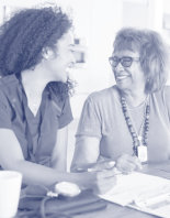 female healthcare worker sitting at table smiling with a senior woman